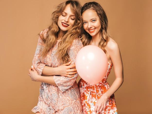 Две улыбающиеся красивые женщины в летних платьях. девочки позируют. модели с разноцветными шарами. веселимся, готовимся к празднованию дня рождения или праздничной вечеринки