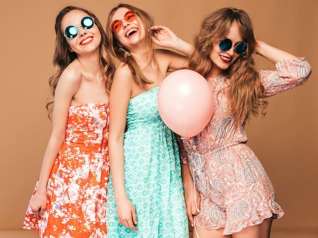 Три улыбающиеся красивые женщины в клетчатой рубашке летней одежды. девочки позируют. модели с разноцветными шарами в солнцезащитные очки. веселимся, готовимся к празднованию дня рождения или праздничной вечеринки