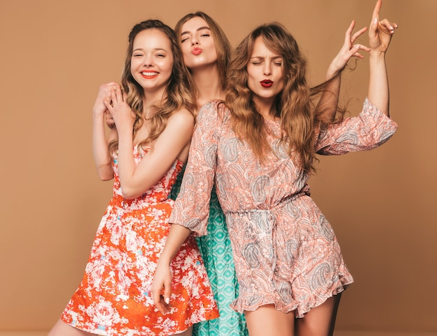 Три молодые красивые улыбающиеся девушки в модных летних повседневных платьях и в солнцезащитных очках. сексуальные беззаботные женщины позируют.