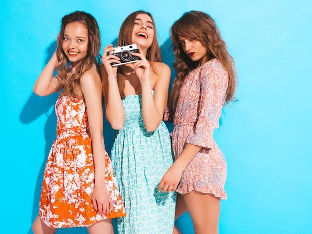 Три молодые красивые улыбающиеся девушки в модных летних разноцветных платьях. сексуальные беззаботные женщины позируют. фотографировать на ретро камеру