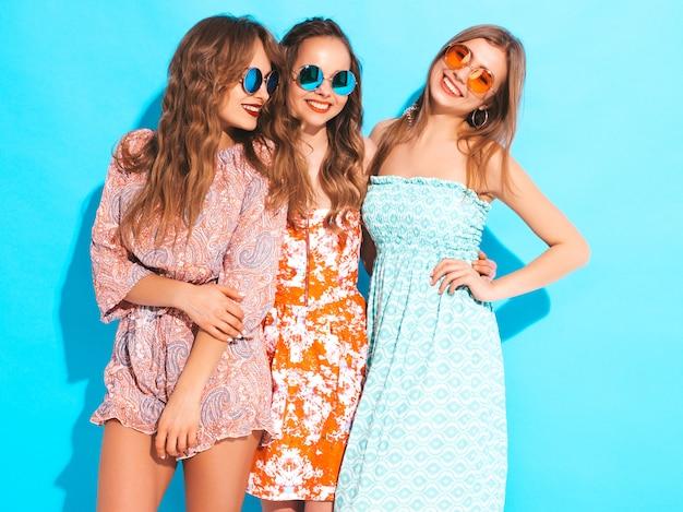 Три молодые красивые улыбающиеся девушки в модных летних разноцветных платьях. сексуальные беззаботные женщины в солнцезащитных очках.