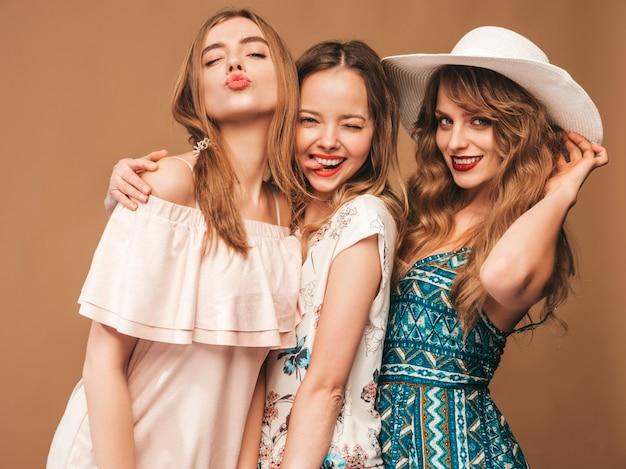 Три молодые красивые улыбающиеся девушки в модных летних повседневных платьях. сексуальные беззаботные женщины позируют.