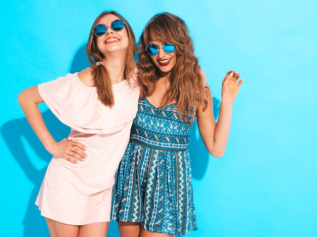 Две молодые красивые улыбающиеся девушки в модных летних платьях и солнцезащитные очки. сексуальные беззаботные женщины позируют.