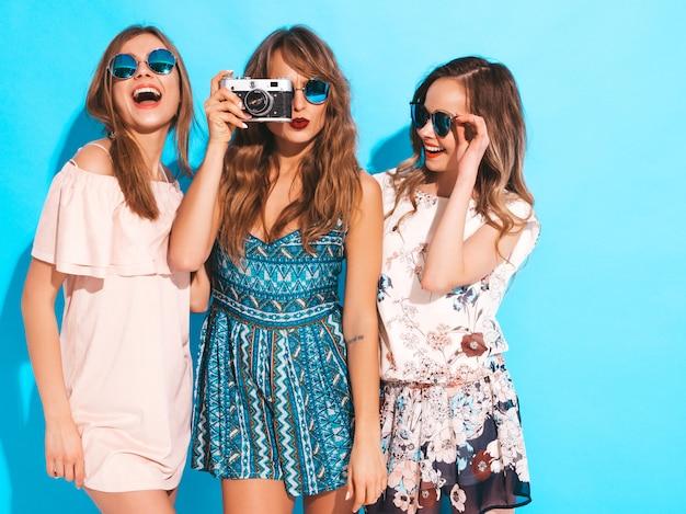 Три молодые красивые улыбающиеся девушки в модных летних повседневных платьях. сексуальные беззаботные женщины позируют. фотографировать на ретро камеру