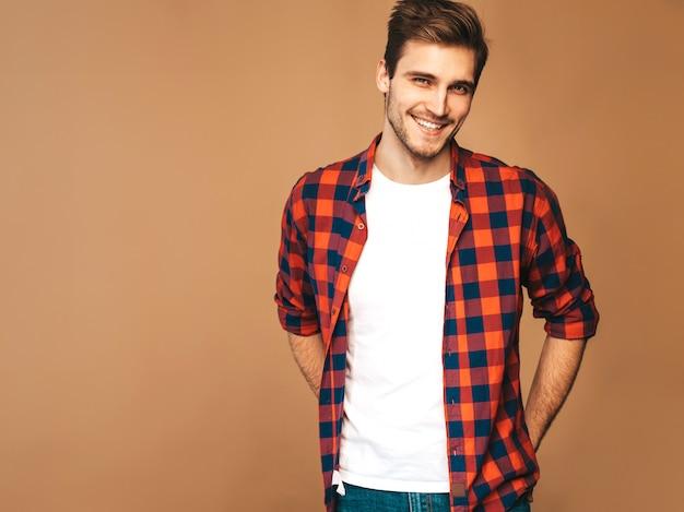 赤い格子縞のシャツに身を包んだハンサムな笑顔スタイリッシュな若い男モデルの肖像画。ファッション男のポーズ