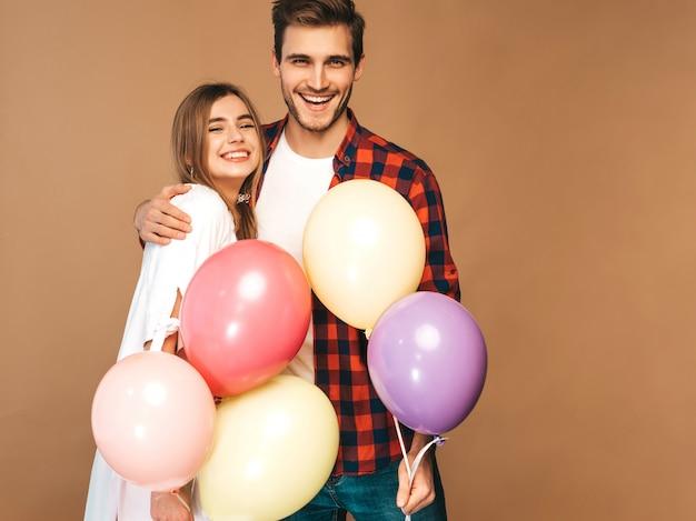 Портрет улыбается красивая девушка и ее красивый парень, холдинг кучу разноцветных шаров и смех. счастливая пара в любви. с днем рождения