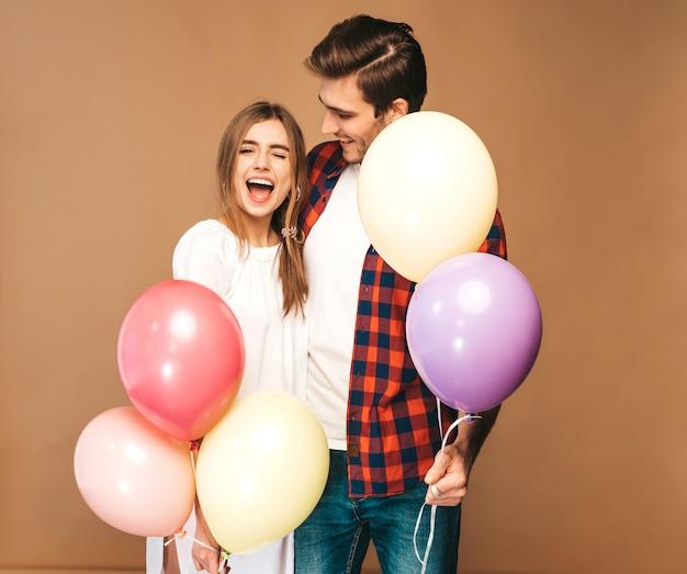 笑顔の美しい少女とカラフルな風船の束を押しながら笑っている彼女のハンサムなボーイフレンドの肖像画。愛の幸せなカップル。お誕生日おめでとうございます