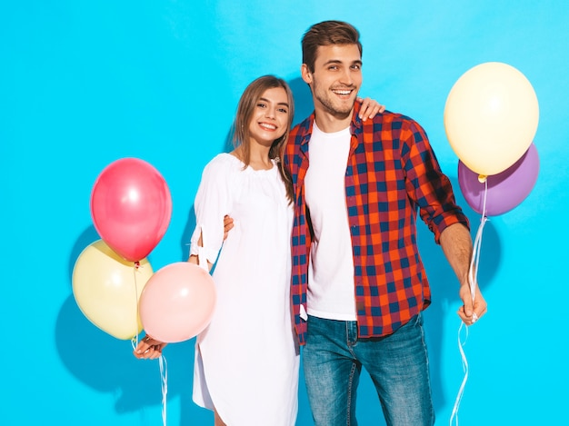 Портрет улыбается красивая девушка и ее красивый парень, холдинг кучу разноцветных шаров и смех. с днем рождения