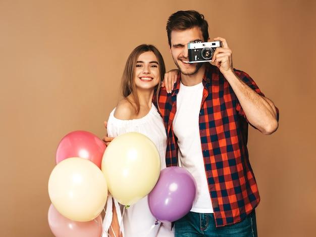 美しい少女とカラフルな風船の束を持って彼女のハンサムなボーイフレンドの笑みを浮かべてください。幸せなカップルは、レトロなカメラで自分の写真を撮る。お誕生日おめでとうございます