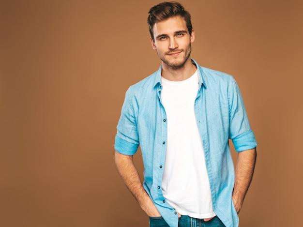 Портрет красивой улыбающейся стильной модели молодого человека оделась в джинсовой одежде. модный мужчина. позирует