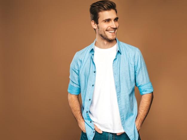青いシャツの服に身を包んだハンサムな笑みを浮かべてスタイリッシュな若い男モデルの肖像画。ファッション男のポーズ