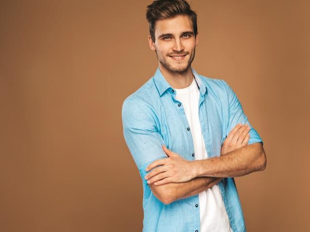 ジーンズ服に身を包んだハンサムな笑みを浮かべてスタイリッシュな若い男モデルの肖像画。ファッション男。ポーズ