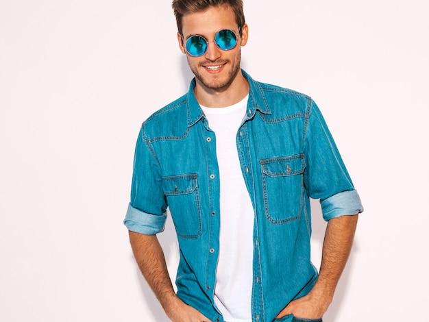Портрет красивой улыбающейся стильной модели молодого человека оделась в джинсовой одежде. модные мужчины носить солнцезащитные очки.