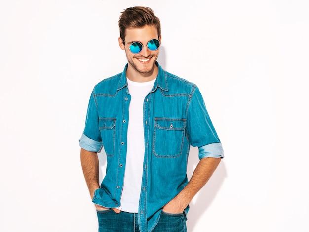 ジーンズの服とサングラスを着てハンサムな笑みを浮かべてスタイリッシュな若い男モデルの肖像画。ファッション男