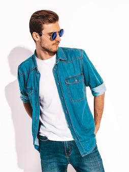 Портрет красивые улыбающиеся стильный молодой человек модель носить джинсовую одежду и очки. модный мужчина