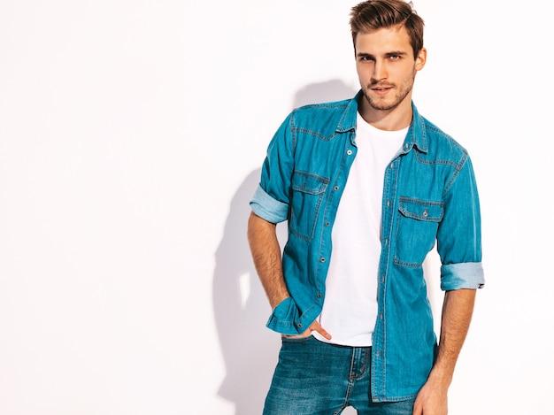 ジーンズの服を着てハンサムな笑顔スタイリッシュな若い男モデルの肖像画。ファッション男