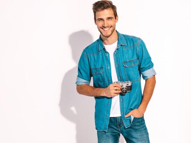 夏のジーンズの服を着てハンサムな笑みを浮かべて男の肖像画。ビンテージ写真カメラを保持しているモデル男性。