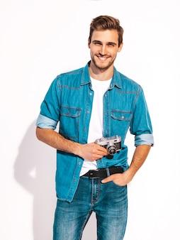 Портрет красавец улыбающегося носить летние джинсы одежды. модельный мужчина фотографируя на старой винтажной камере фото.