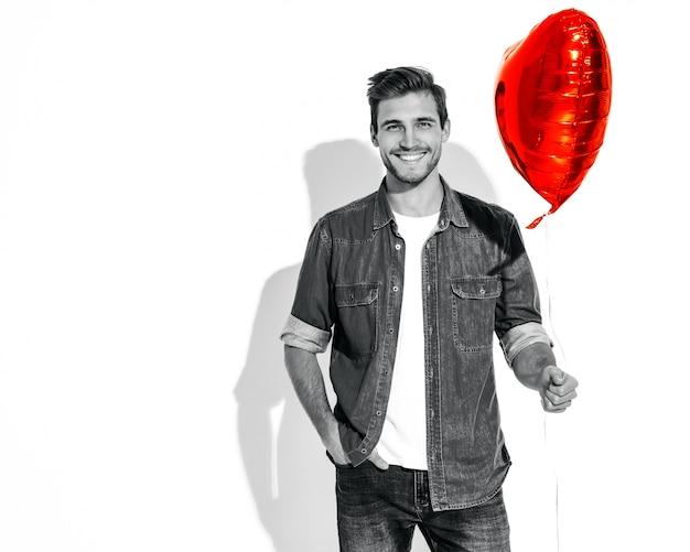 Портрет красивой улыбающейся стильной модели человека, одетого в джинсовую одежду. мода мужчина держит воздушный шар в форме сердца.