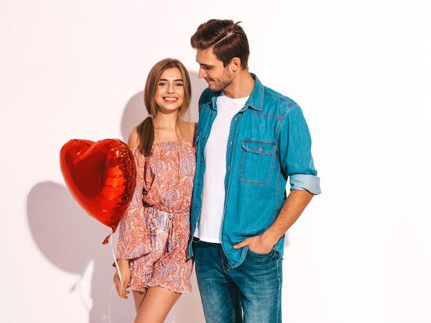 Портрет улыбается красивая девушка и ее красивый парень, держа воздушные шары в форме сердца и смех. счастливая пара в любви. счастливого дня святого валентина.