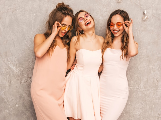 Три молодые красивые улыбающиеся девушки в модных летних светло-розовых платьях. сексуальные беззаботные женщины позируют. позитивные модели в круглых солнечных очках с удовольствием