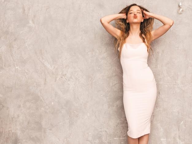 トレンディな夏の淡いピンクのドレスで美しい笑顔少女の肖像画。セクシーな屈託のない女性がポーズします。楽しいとキスを与える肯定的なモデル