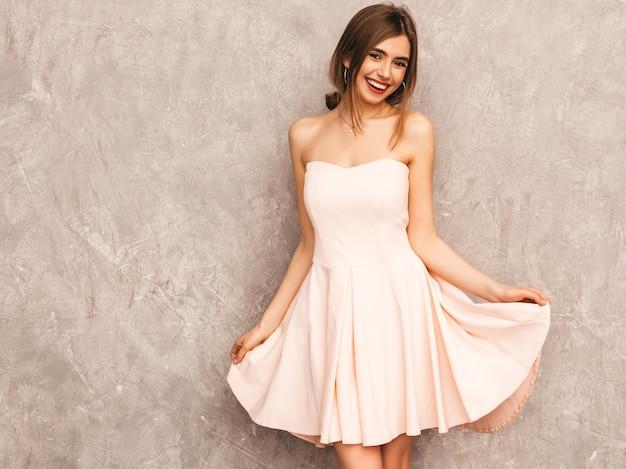 トレンディな夏の淡いピンクのドレスで美しい笑顔少女の肖像画。セクシーな屈託のない女性がポーズします。楽しいポジティブモデル