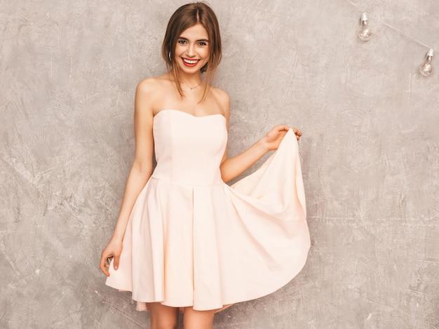 トレンディな夏の淡いピンクのドレスで美しい笑顔少女の肖像画。セクシーな屈託のない女性がポーズします。楽しいポジティブモデル。ダンシング