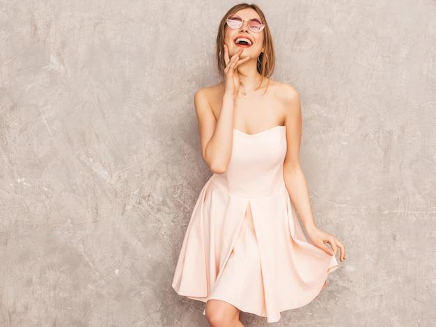 トレンディな夏の淡いピンクのドレスで美しい笑顔少女の肖像画。セクシーな屈託のない女性がポーズします。楽しいポジティブモデル。丸いサングラスで踊る