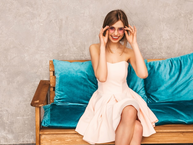 トレンディな夏の淡いピンクのドレスで美しい笑顔少女の肖像画。明るい青いソファに座っているセクシーな屈託のない女性。豪華なインテリアでポーズ
