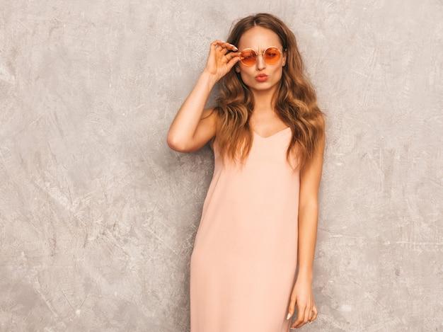 トレンディな夏の淡いピンクのドレスで美しい笑顔少女の肖像画。セクシーな屈託のない女性がポーズします。ラウンドサングラスで楽しんでいる肯定的なモデル
