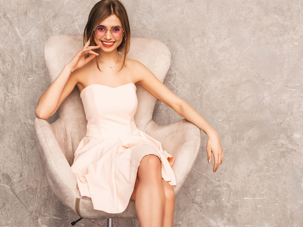 トレンディな夏の淡いピンクのドレスで美しい笑顔少女の肖像画。ベージュの椅子に座っているセクシーな屈託のない女性。豪華なインテリアでポーズ