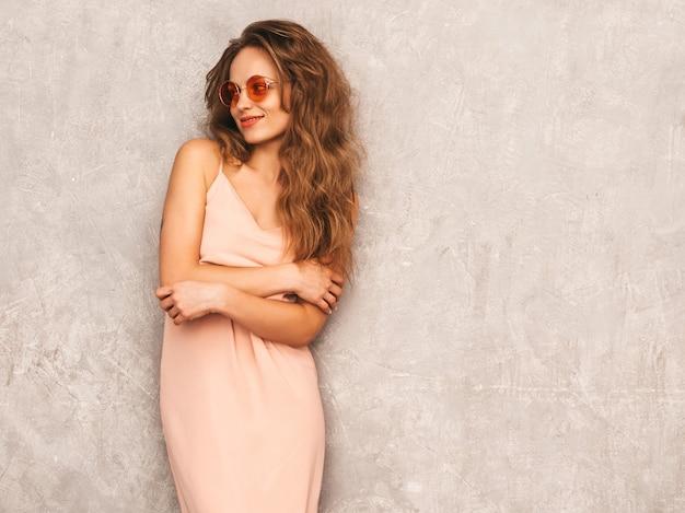 トレンディな夏の淡いピンクのドレスで美しい笑顔少女の肖像画。セクシーな屈託のない女性がポーズします。ラウンドサングラスで楽しんでいるポジティブなモデル。自分を抱き締める