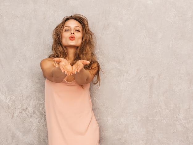 トレンディな夏の淡いピンクのドレスで美しい笑顔少女の肖像画。セクシーな屈託のない女性がポーズします。楽しんでいる肯定的なモデル。空気キスを与える