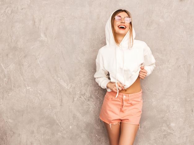 トレンディな夏のスポーツ服の美しい笑顔少女の肖像画。セクシーな屈託のない女性がポーズします。サングラスで楽しんでいるポジティブなモデル