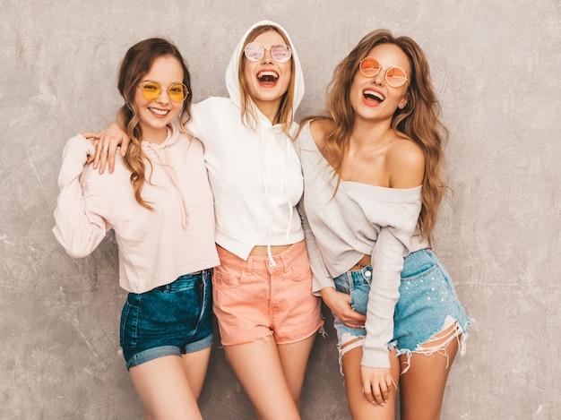 Три молодые красивые улыбающиеся девушки в модной летней спортивной одежды. сексуальные беззаботные женщины позируют. позитивные модели в круглых очках веселятся. в обнимку