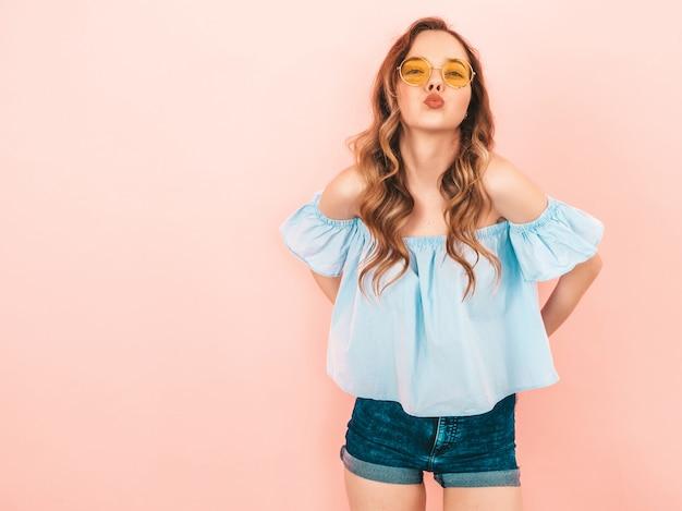 丸いサングラスで美しい笑顔かわいいモデルの肖像画。夏のカラフルな服の女の子。モデルのポーズ。キスをする