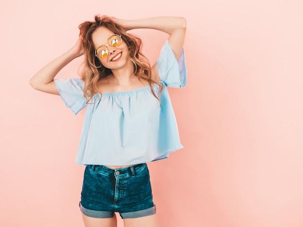 丸いサングラスで美しい笑顔かわいいモデルの肖像画。夏のカラフルな服の女の子。モデルのポーズ。彼女の髪と遊ぶ
