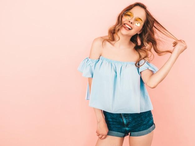 丸いサングラスで美しい笑顔かわいいモデルの肖像画。夏のカラフルな服の女の子。モデルのポーズ