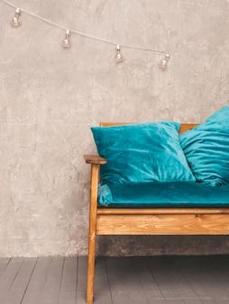 スタイリッシュな布張りの青と木製のモダンなソファと灰色の壁のインテリア