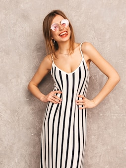 トレンディな夏のシマウマのドレスで美しい笑顔少女の肖像画。セクシーな屈託のない女性がポーズします。ラウンドサングラスで楽しんでいる肯定的なモデル