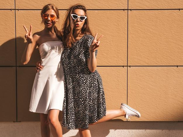 Две молодые красивые улыбающиеся битник девушки в модном летнем платье.