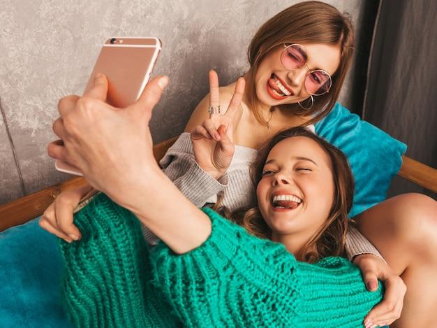 Две молодые красивые улыбающиеся великолепные девушки в модной летней одежде. сексуальные беззаботные женщины, позирующие в интерьере и делающие селфи. позитивные модели с удовольствием со смартфоном. показ мира