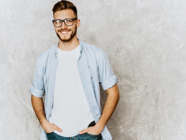 カジュアルなシャツ服を着ているハンサムな笑顔若い男モデルの肖像画。眼鏡でポーズをとってファッションスタイリッシュな男