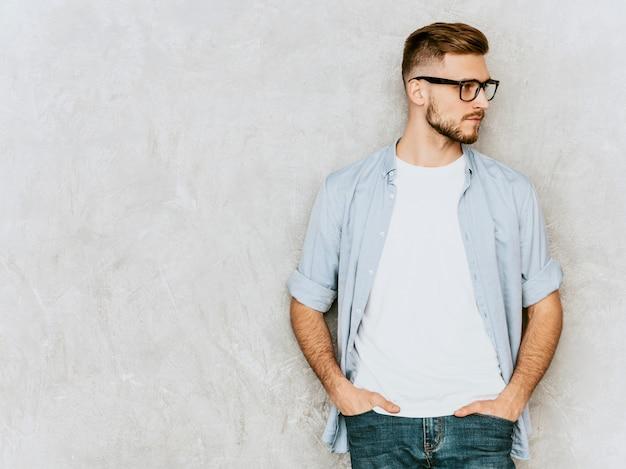 カジュアルなシャツ服を着ているハンサムな深刻な若い男モデルの肖像画。眼鏡でポーズをとってファッションスタイリッシュな男