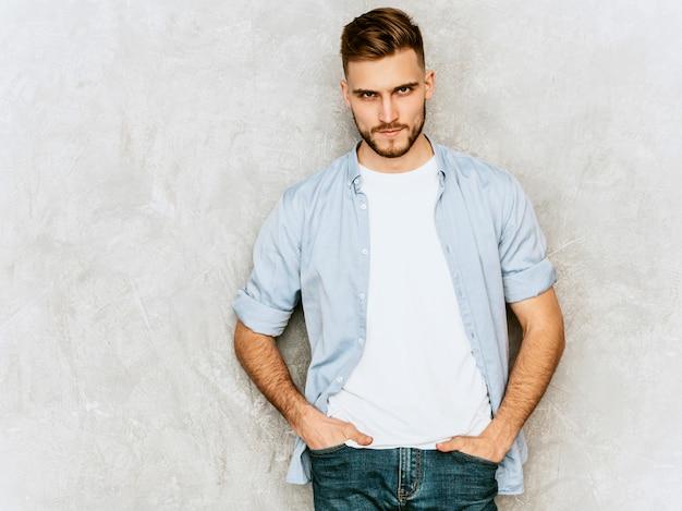 Портрет красивой молодой модели человека, носящего повседневную одежду рубашки. мода стильный мужчина позирует