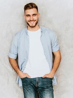 カジュアルなシャツ服を着ているハンサムな笑顔若い男モデルの肖像画。ファッションスタイリッシュな男のポーズ
