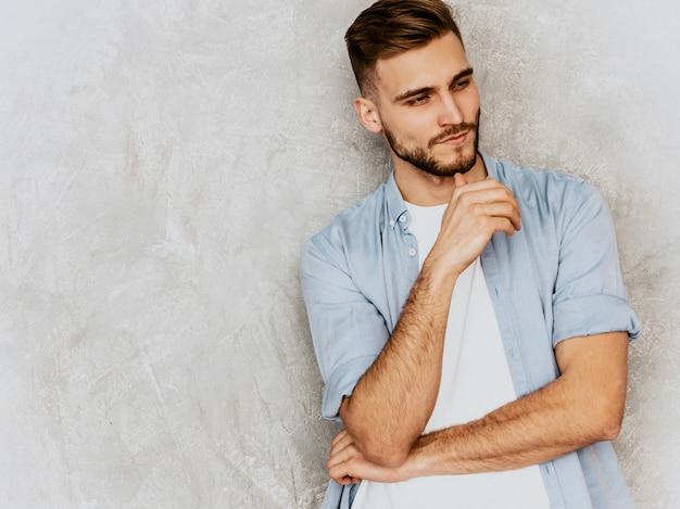 カジュアルなシャツ服を着ているハンサムな若い男モデルの肖像画。ファッションスタイリッシュな男のポーズ
