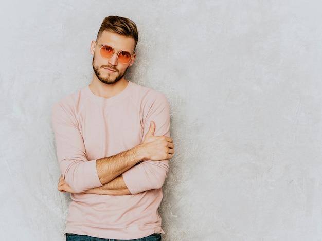 カジュアルな夏のピンクの服を着てハンサムな深刻な若い男モデルの肖像画。ファッションスタイリッシュな男のポーズ