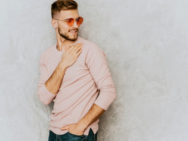 カジュアルな夏のピンクの服を着てハンサムな笑みを浮かべて若い男モデルの肖像画。丸いサングラスでポーズをとってファッションスタイリッシュな男